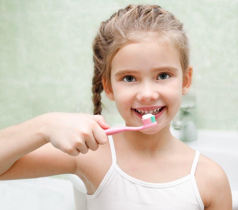 微笑的逗人喜爱的小女孩掠过的牙 库存图片