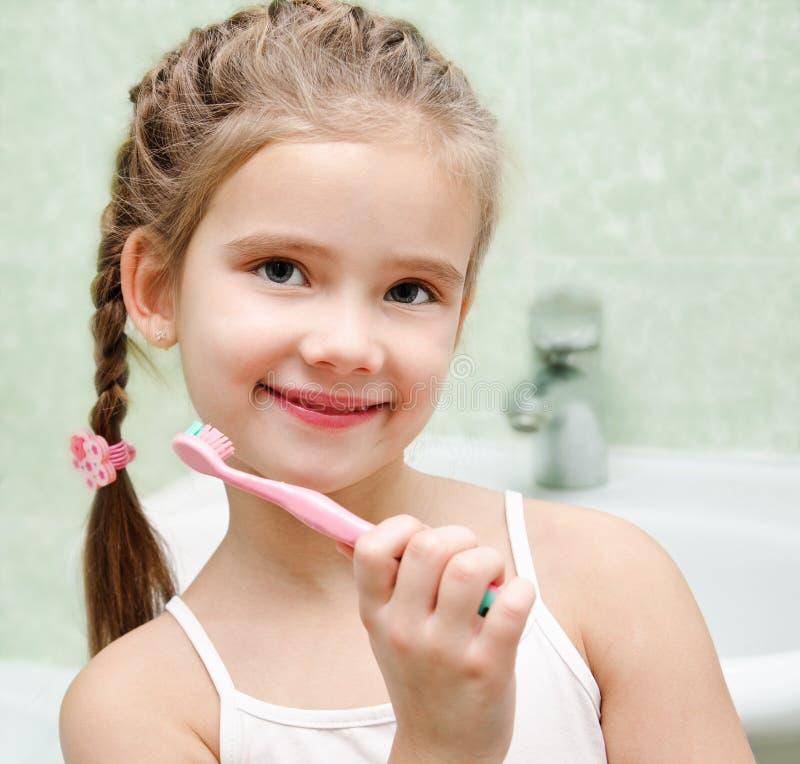 微笑的逗人喜爱的小女孩掠过的牙 免版税图库摄影