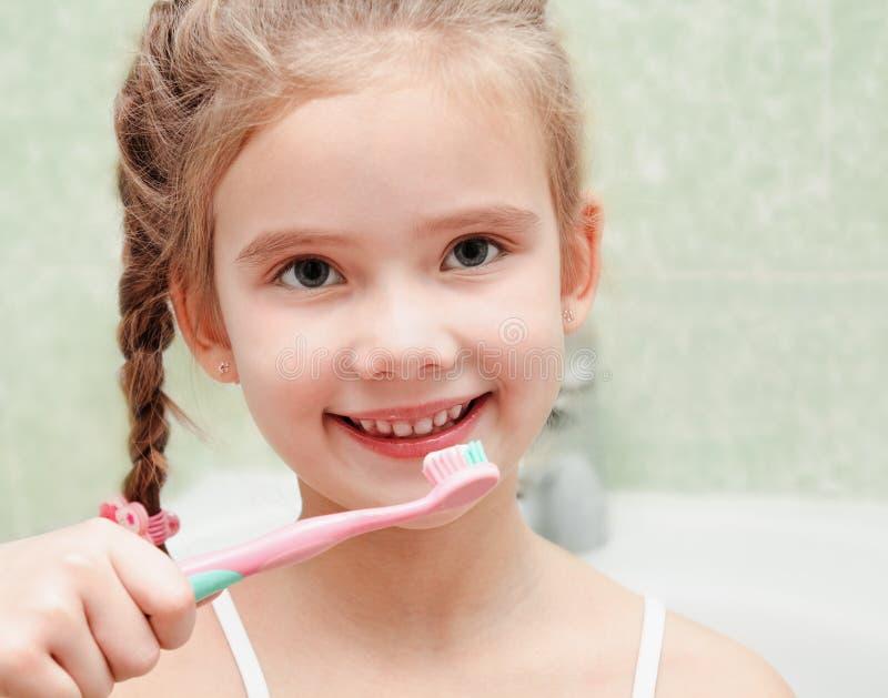 微笑的逗人喜爱的小女孩掠过的牙 免版税库存图片
