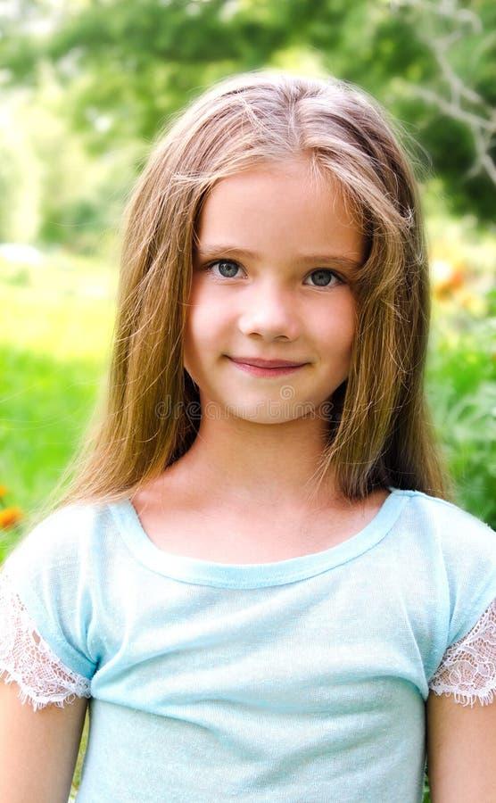 微笑的逗人喜爱的小女孩画象在夏日 免版税库存照片