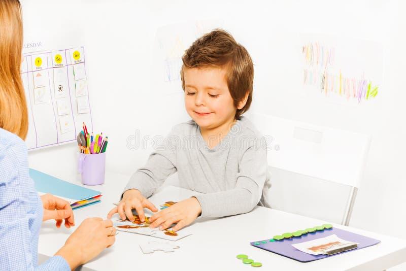 微笑的逗人喜爱的男孩打与父母的开发的比赛 免版税图库摄影