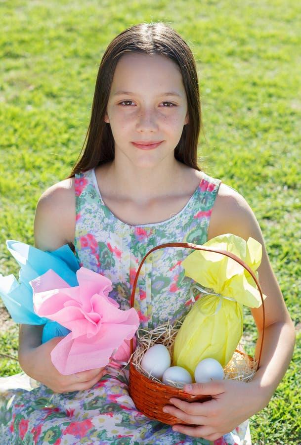微笑的逗人喜爱的青少年的女孩用在五颜六色的纸e的复活节巧克力 库存照片