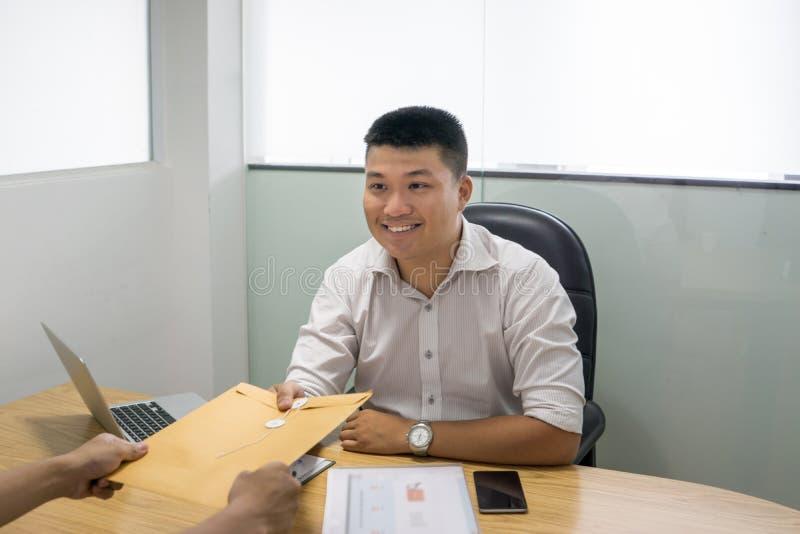 微笑的采访者从面试的候选人接受CV 免版税库存照片
