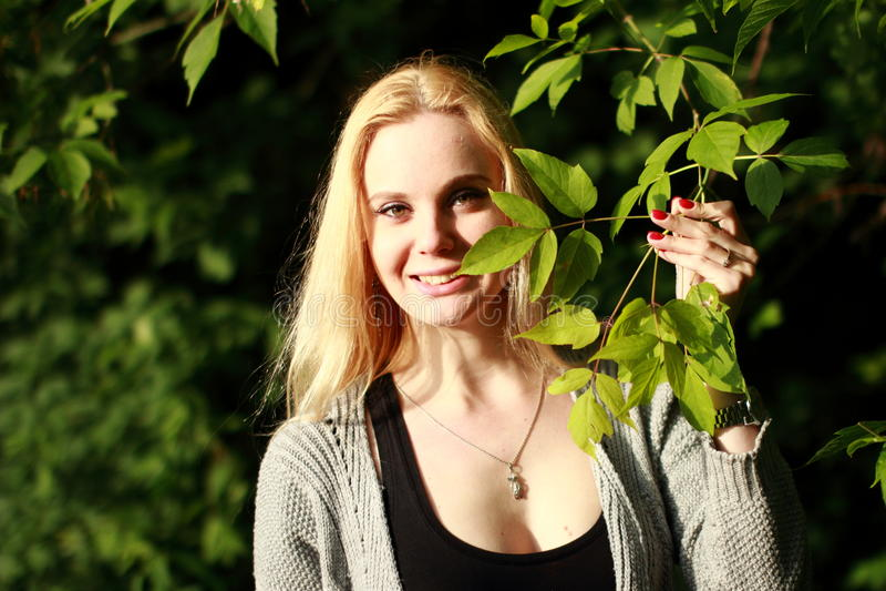 微笑的金发碧眼的女人在晴朗的森林里 库存图片
