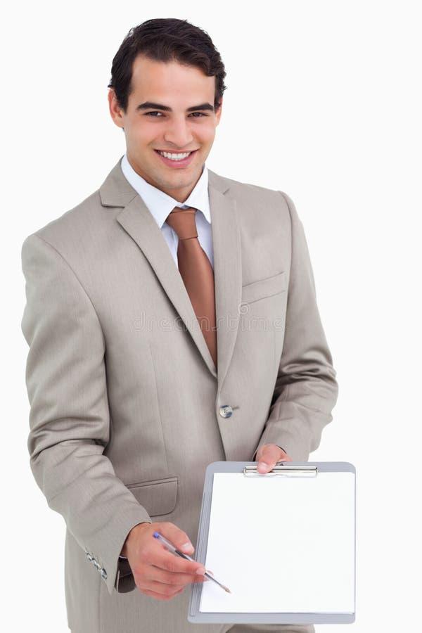 微笑的销售人员请求签名 免版税库存图片