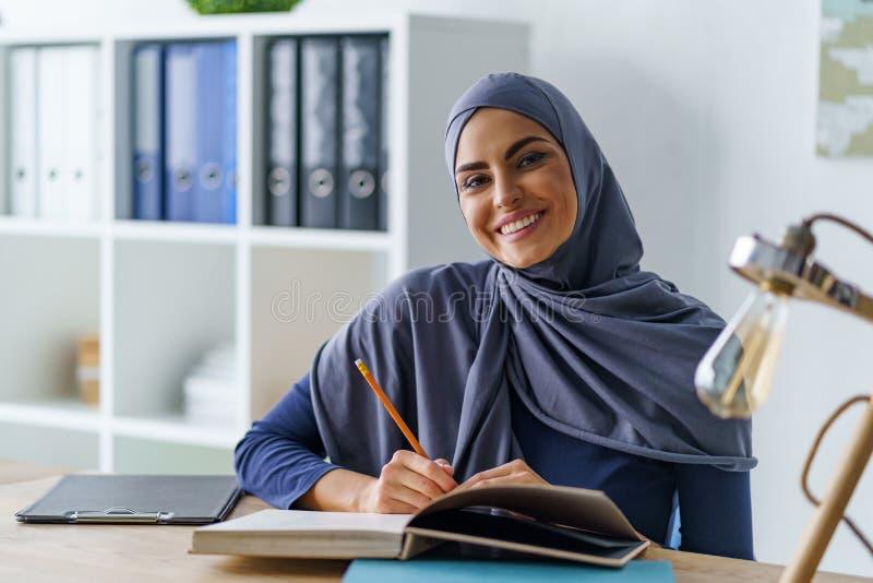 微笑的阿拉伯妇女坐 库存照片
