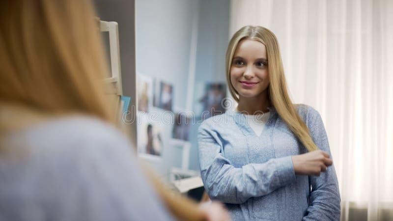 微笑的青少年满意对软和健康头发,敬佩她的出现 库存照片