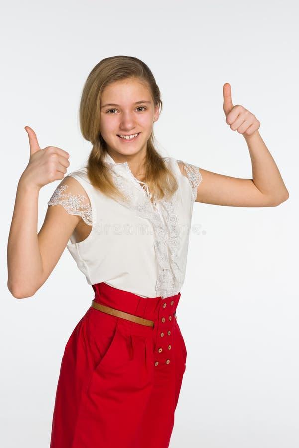 微笑的青少年的女孩举行她的赞许 免版税库存照片