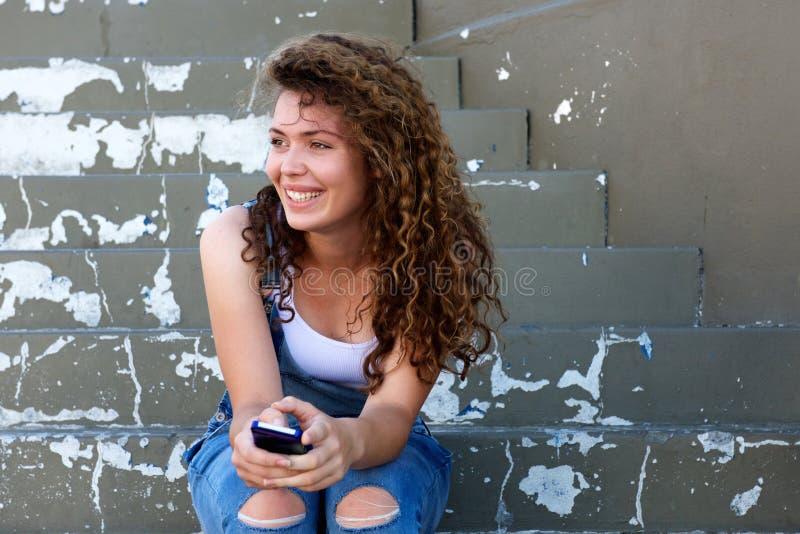 微笑的青少年的女孩拿着电话和坐步 免版税库存图片