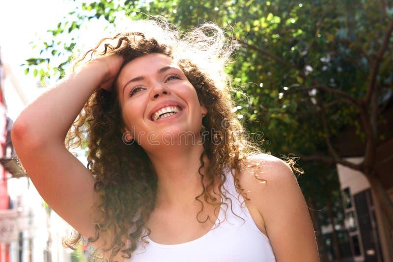 微笑的青少年的女孩用在头发常设外部的手 库存图片