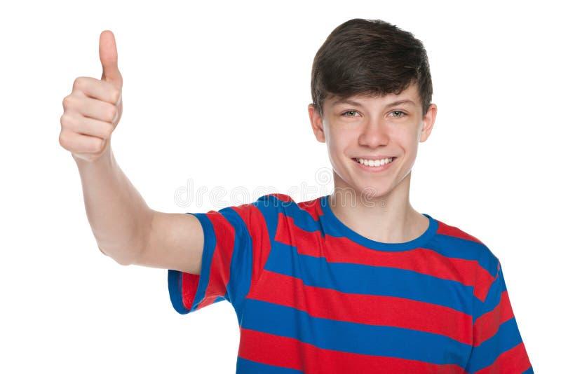 微笑的青少年的男孩举行他的赞许 免版税库存照片