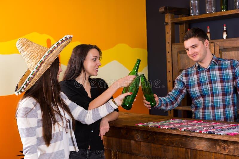 微笑的青年人使叮当响的瓶公司啤酒,当时 库存图片