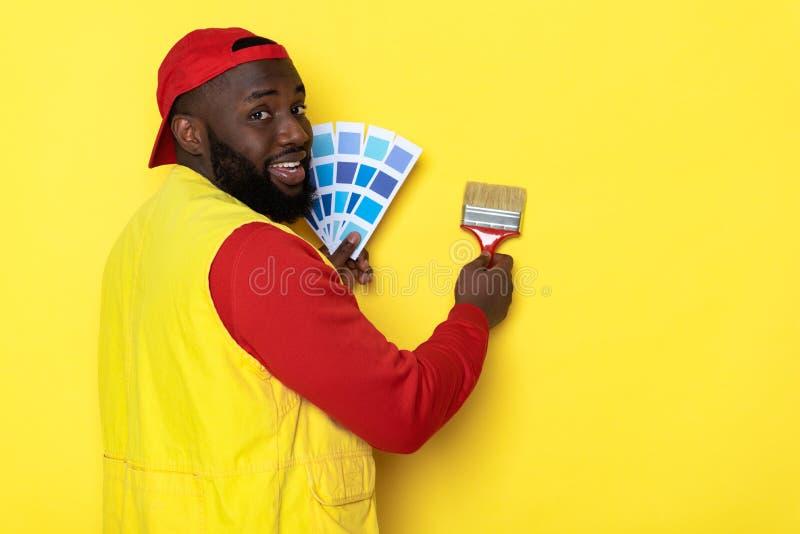微笑的非洲人藏品油漆刷和调色板侧视图在胳膊 库存图片
