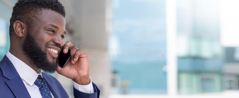 微笑的非洲商人画象谈话由电话外面与拷贝空间 库存照片