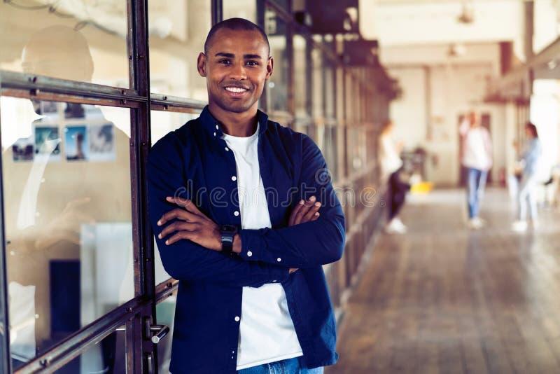 微笑的非裔美国人的商人画象有运作在背景中的董事的 库存照片