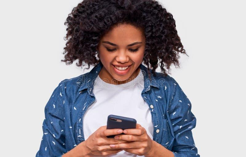 微笑的非裔美国人的年轻女人画象的室内关闭使用手机的,对她的朋友的传讯 免版税库存照片