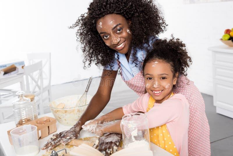 微笑的非裔美国人的母亲和女儿一起揉的和滚动的面团 库存图片