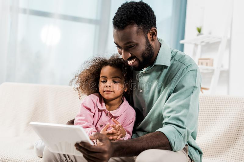 微笑的非裔美国人的父亲和孩子使用数字片剂,当坐时 库存图片