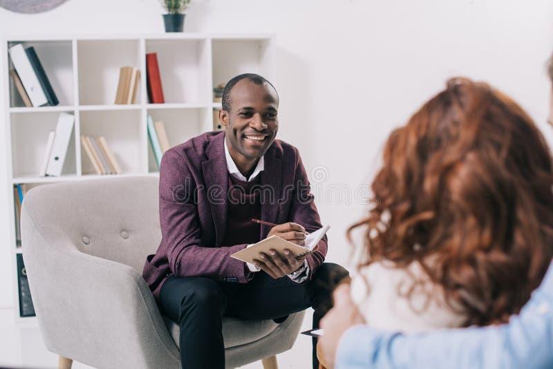 微笑的非裔美国人的精神病医生谈话 免版税库存图片