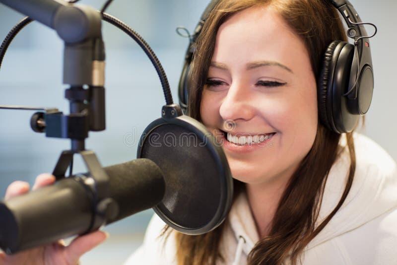微笑的骑师,当使用耳机和话筒在收音机St时 免版税库存图片