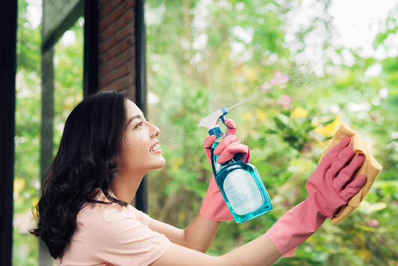 微笑的年轻亚裔妇女主妇洗涤一个窗口 库存照片