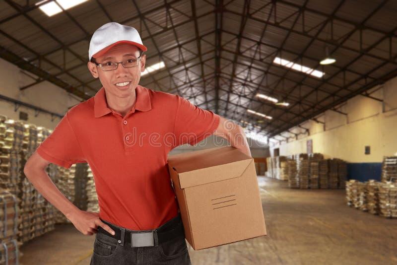 微笑的年轻亚洲男性邮政递送传讯者 库存图片