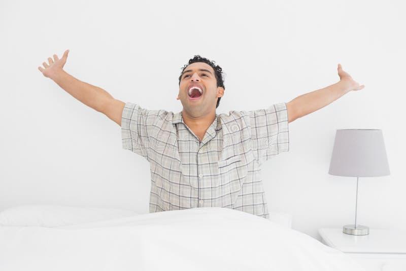 微笑的年轻人在床上的舒展他的胳膊 免版税库存照片