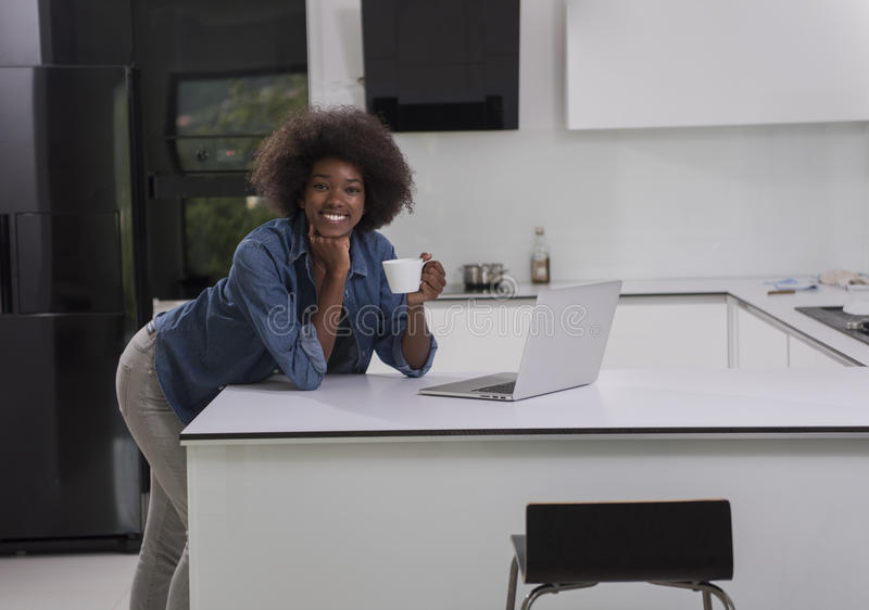 微笑的黑人妇女在现代厨房里 库存图片