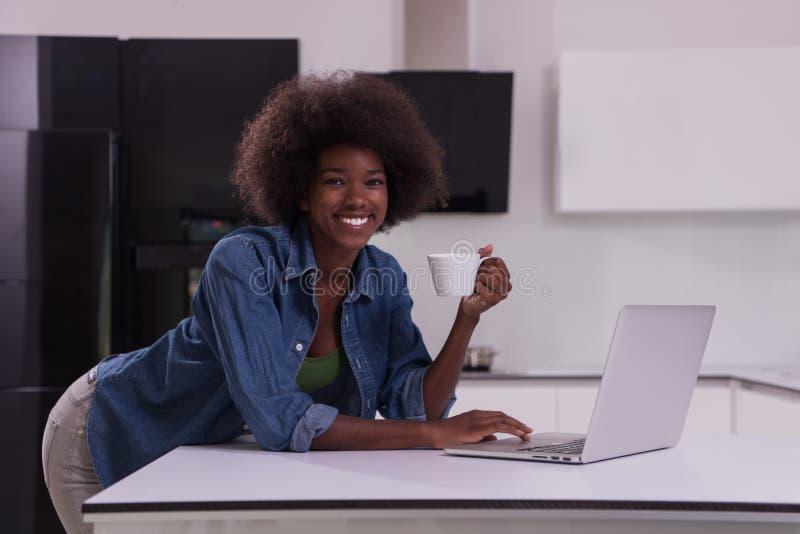 微笑的黑人妇女在现代厨房里 库存照片