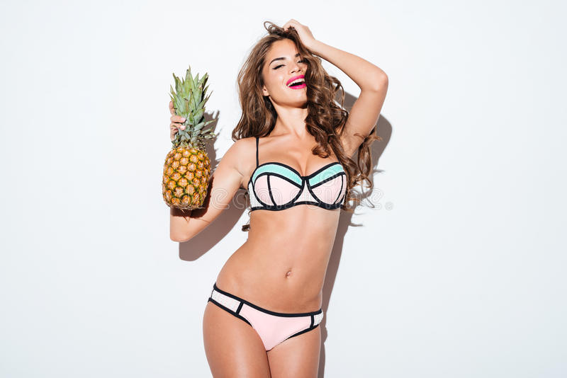 微笑的年轻人相当举行菠萝和摆在的性感的女孩 免版税图库摄影