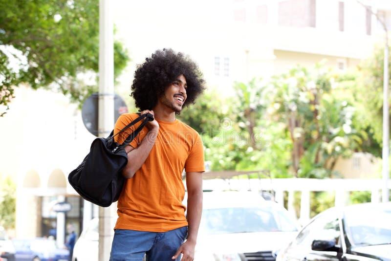 微笑的黑人运载的旅行袋子 库存照片