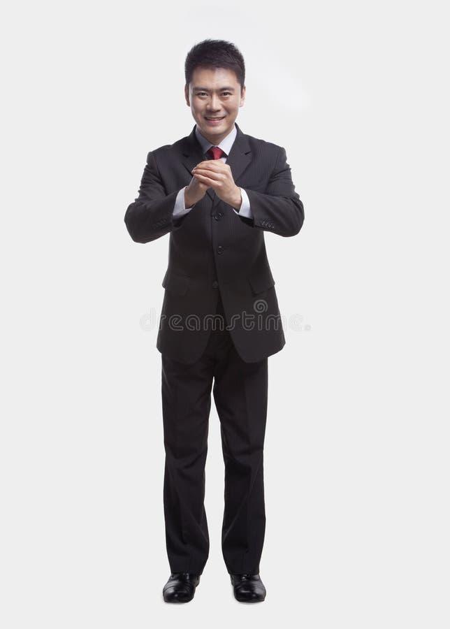 微笑的年轻商人用手扣紧了一起鞠躬往照相机,演播室射击 库存照片