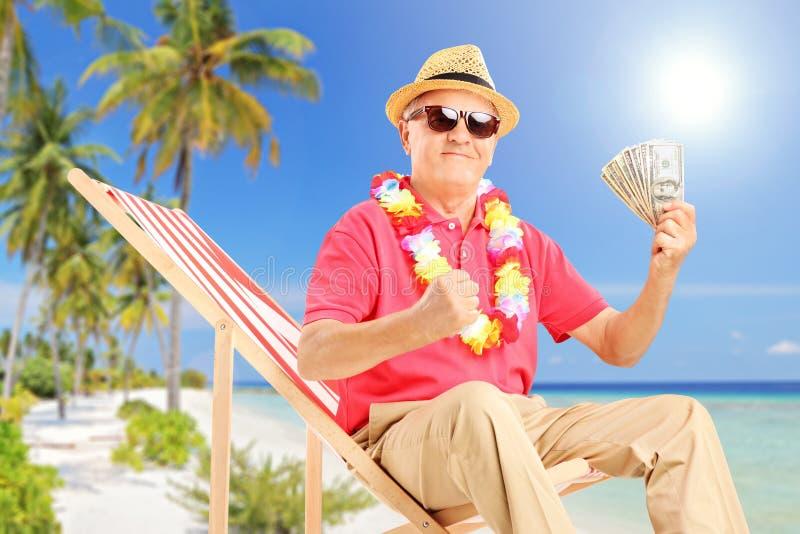 微笑的绅士坐海滩睡椅和拿着美元 免版税库存图片
