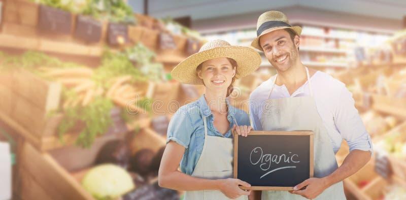 微笑的年轻夫妇画象的综合图象举行文字的与有机文本一起提名 库存照片