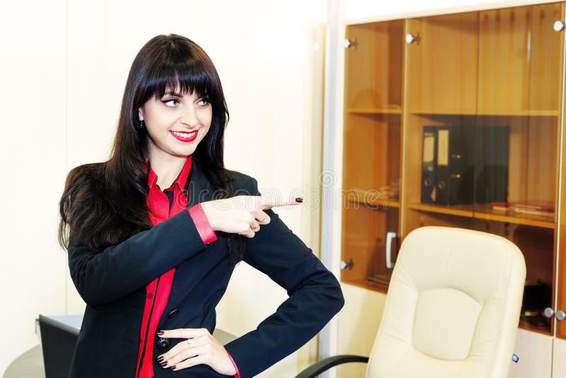 微笑的年轻女实业家在方向显示一个手指 库存照片