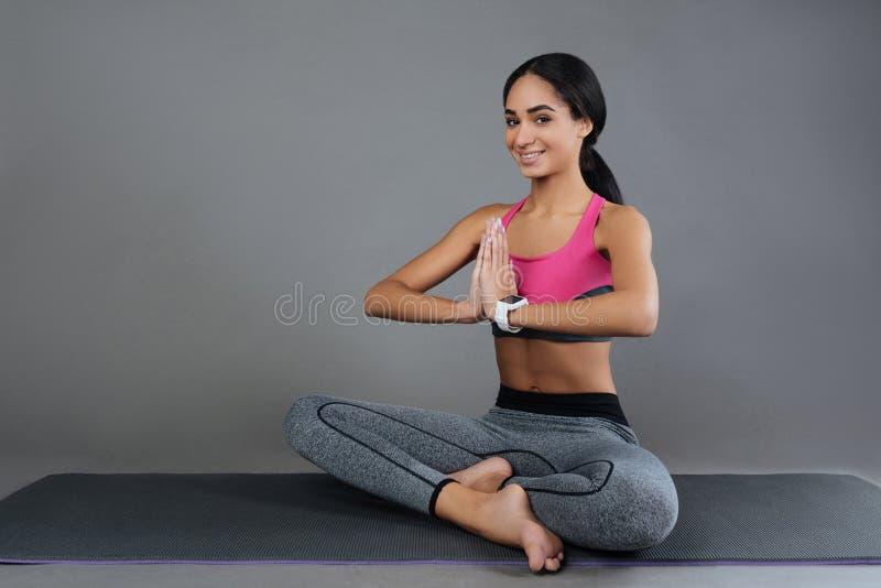 微笑的年轻女性,当做瑜伽时 免版税库存图片