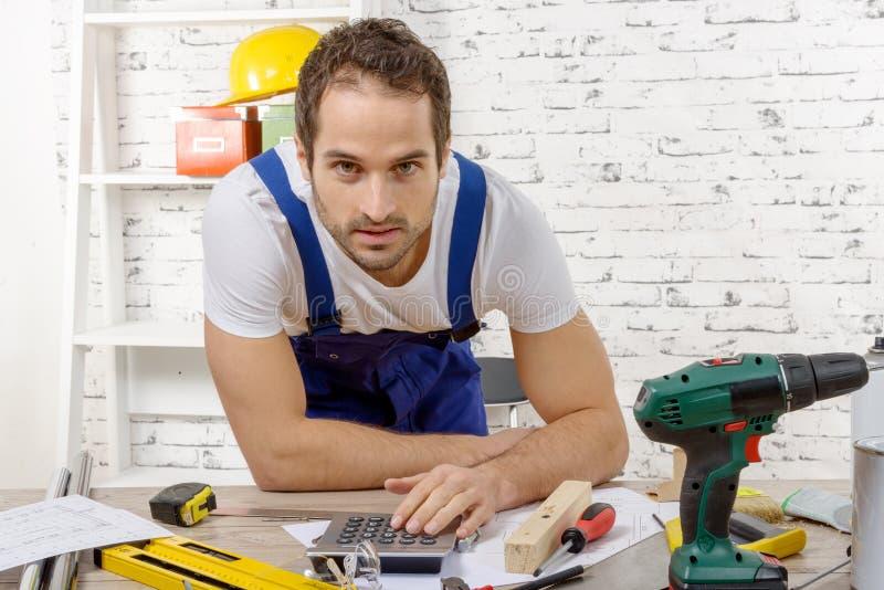 微笑的年轻木匠在他的车间 库存照片