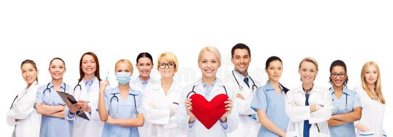 微笑的医生和护士有红色心脏的 免版税库存照片