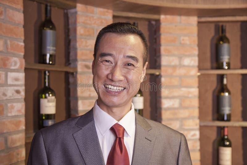 微笑的更老的商人支持的酒瓶画象  库存图片