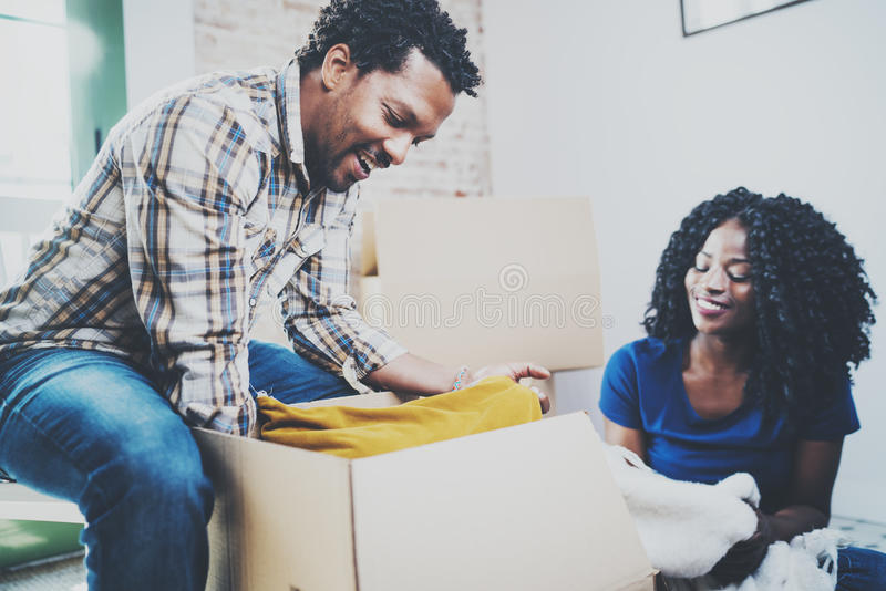 微笑的年轻非洲黑人一起结合移动的箱子入新的家和做成功的生活 快乐的系列 库存照片
