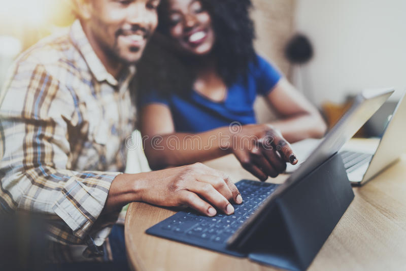 微笑的年轻非洲夫妇有休息在家:坐在桌上的黑人,使用触板和笑 免版税库存照片