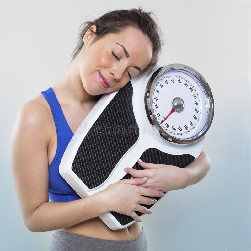 微笑的20s女孩照料她的公斤或磅与她的健康最好的朋友 免版税库存图片