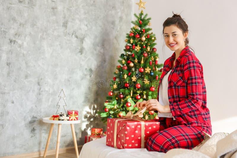 微笑的beautifu妇女佩带的睡衣在圣诞节早晨 免版税图库摄影
