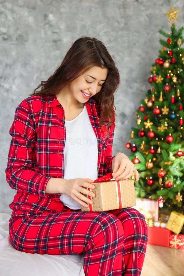 微笑的beautifu妇女佩带的睡衣在圣诞节早晨 库存照片