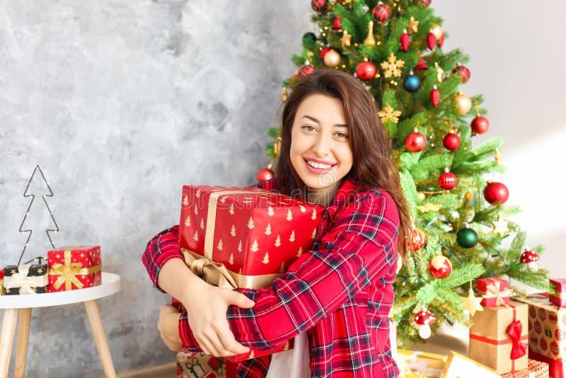 微笑的beautifu妇女佩带的睡衣在圣诞节早晨 免版税库存图片