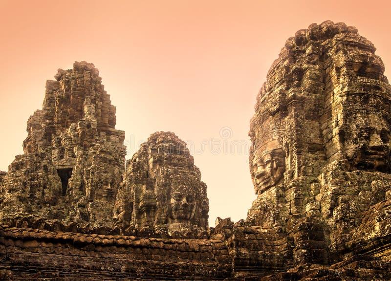 微笑的Buddhas石雕象在吴哥城,暹粒,日出的柬埔寨复合体的  免版税库存图片