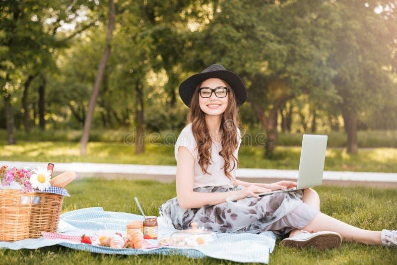 微笑相当使用在野餐的少妇膝上型计算机在公园 库存图片