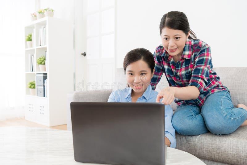 微笑相当使用移动计算机的女性朋友 免版税库存图片
