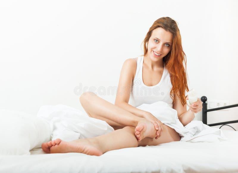 微笑相当在家把奶油放的少妇在腿上 免版税库存图片