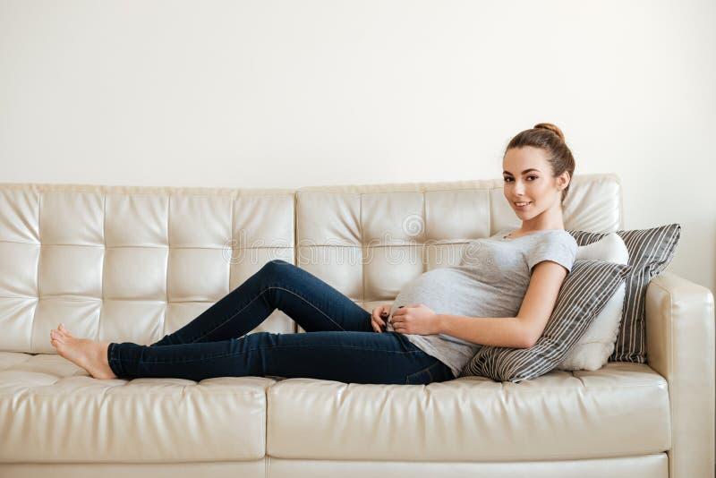 微笑相当说谎和基于沙发的怀孕的少妇 免版税图库摄影